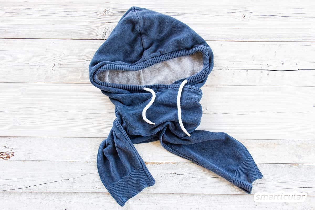 Ein alter Kapuzenpullover, der vielleicht schon ein paar Löcher hat, muss nicht im Müll landen. Du kannst ihn upcyceln und eine kuschelige Schalmütze daraus nähen.