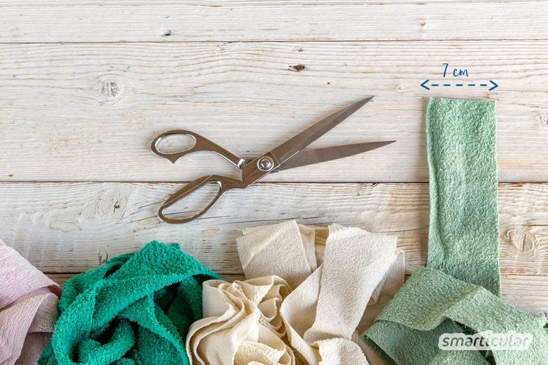 Ein Badteppich lässt sich ganz einfach selber machen. Dafür werden alte Handtücher in Streifen geschnitten und ein Teppich daraus geflochten.